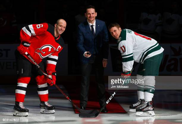 Former New Jersey Devil Patrik Elias drops the ceremonial first puck between Andy Greene and Zach Parise of the Minnesota Wild prior to their game on...