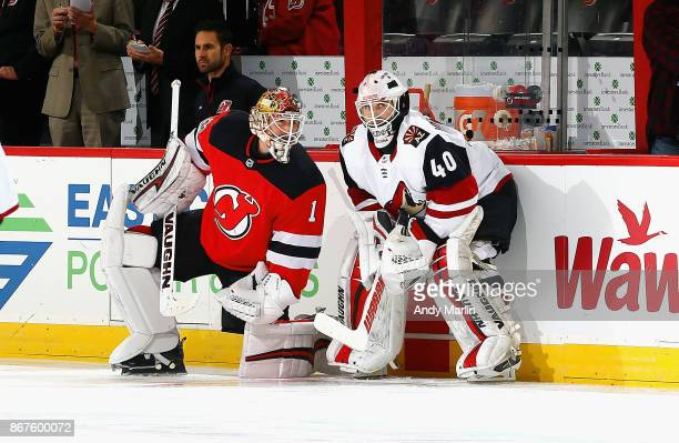 Former New Jersey Devil Scott Wedgewood of the Arizona Coyotes talks with Keith Kinkaid of the New Jersey Devils during pregame warmups prior to the...