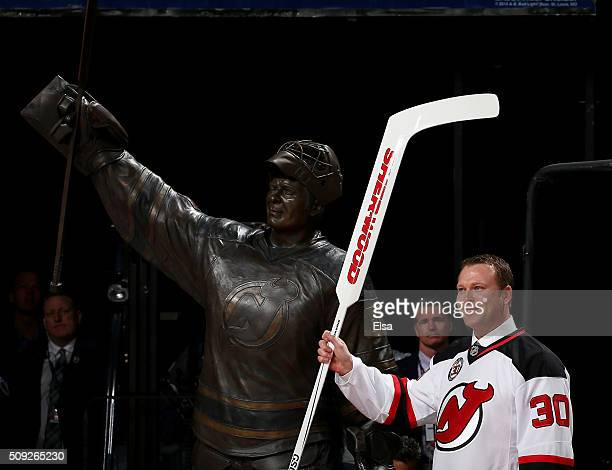 Former New Jersey Devils goaltender Martin Brodeur poses next to his statue during his jersey retirement ceremony before the game between the New...
