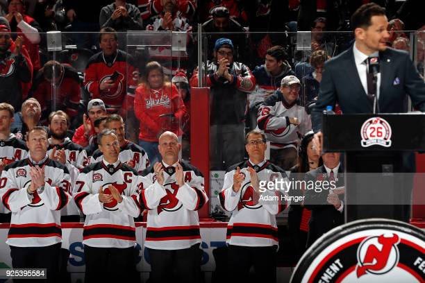 Former New Jersey Devils players Martin Brodeur Scott Niedermayer Ken Daneyko and Scott Stevens applaud Patrik Elias during his jersey retirement...