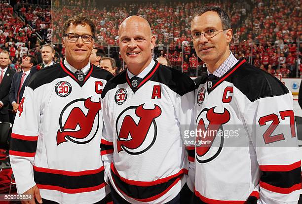 Former New Jersey Devils Scott Stevens Ken Daneyko and Scott Niedermayer pose for a photo during the ceremony celebrating the retirement of his...