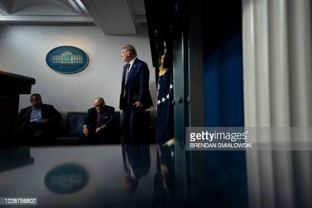 Former New Jersey Governor Chris Christie and former New York City Mayor Rudy Giuliani wait for US President Donald Trump during a briefing at the...