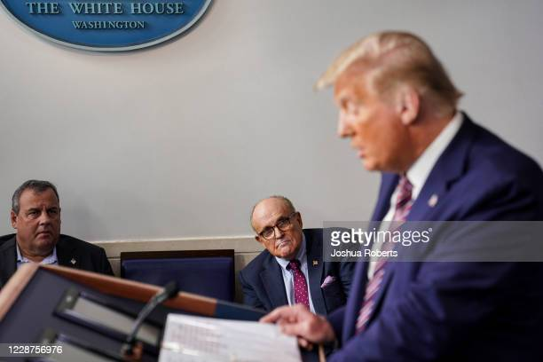 Former New Jersey Governor Chris Christie and former New York Mayor Rudy Giuliani listen as U.S. President Donald Trump speaks during a news...