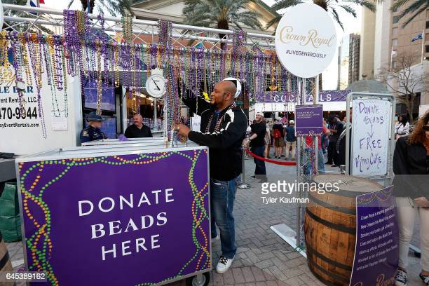 Former New Orleans Saints running back Deuce McAllister collects donated Mardi Gras beads in exchange for King Cakes at the Crown Royal popup event...