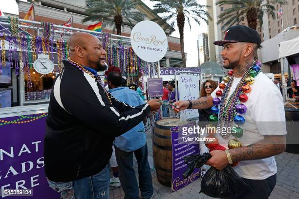 Former New Orleans Saints running back Deuce McAllister generously accepts donated Mardi Gras beads in exchange for King Cakes at the Crown Royal...