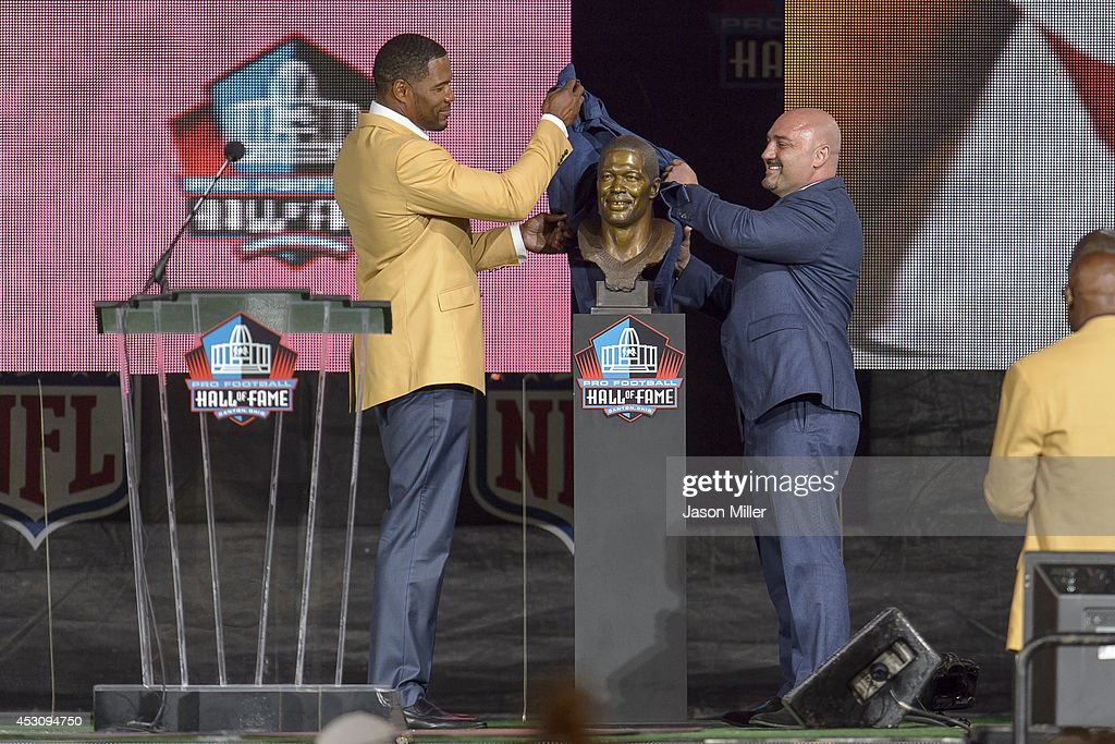 Former New York Giants defensive end Michael Strahan, left, unveils his bust with his friend Jay Glazer, right, during the NFL Class of 2014 Pro Football Hall of Fame Enshrinement Ceremony at Fawcett Stadium on August 2, 2014 in Canton, Ohio.