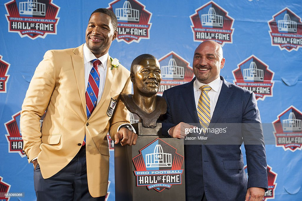 Former New York Giants defensive end Michael Strahan, left, with his bust and his friend Jay Glazer, right, during the NFL Class of 2014 Pro Football Hall of Fame Enshrinement Ceremony at Fawcett Stadium on August 2, 2014 in Canton, Ohio.