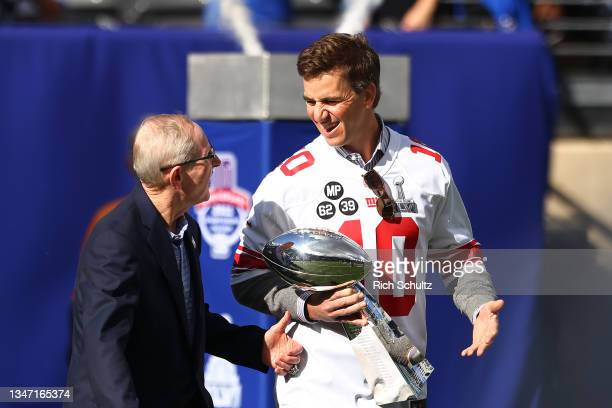 Former New York Giants quarterback Eli Manning and former head coach Tom Coughlin walk onto the field carrying the Vince Lombardi Trophy during a...