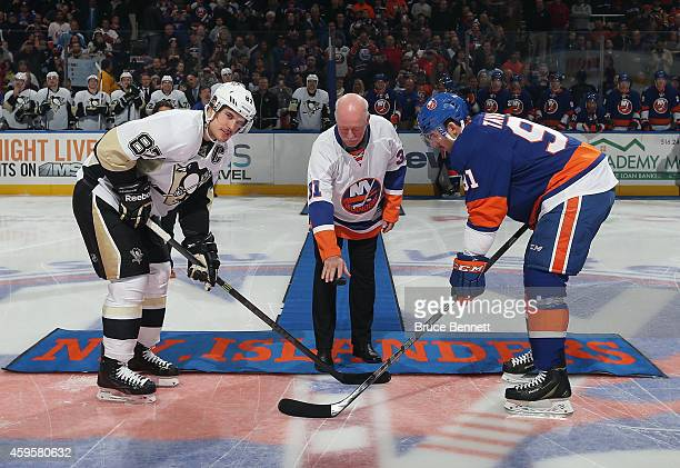 Former New York Islander Billy Smith is honored prior to the Islanders game against the Pittsburgh Penguins and drops the puck between Sidney Crosby...