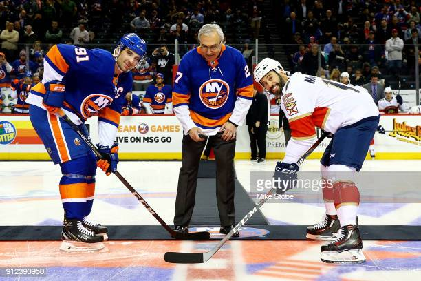Former New York Islander John Tonelli participates in a cermonial puck drop with John Tavares of the New York Islanders and Derek MacKenzie of the...