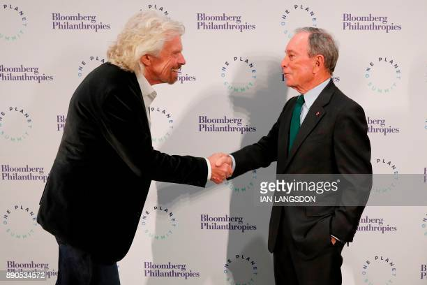 Former New York mayor and United Nations special envoy for cities and climate change Michael Bloomberg shakes hands with British businessman and...