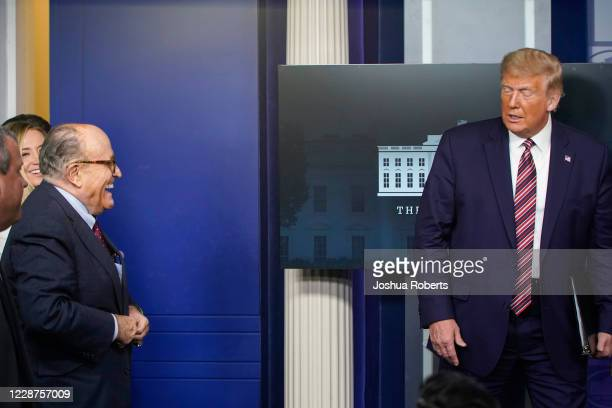 Former New York Mayor Rudy Giuliani stands as US President Donald Trump arrives for a news conference in the Briefing Room of the White House on...