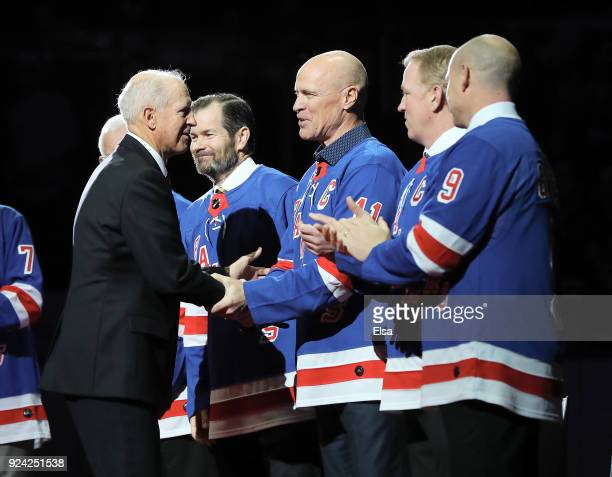 Former New York Rangers Jean Ratelle speaks with former players Mark Messier Brian Leetch and Adam Graves before Ratelle's jersey retirement ceremony...