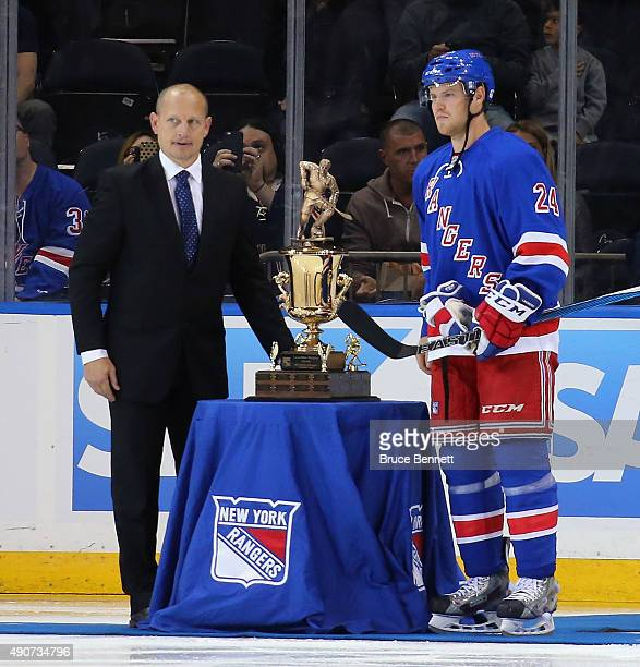 Former New York Rangers player Adam Graves presents the LarsErik Sjoberg award to Oscar Lindberg prior to the game against the Boston Bruins at...