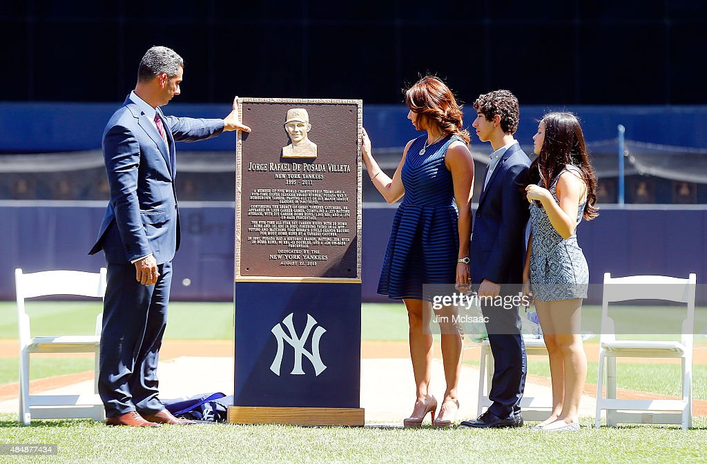 Former New York Yankee Jorge Posada looks at his Monument Park plaque with his wife Laura, son Jorge and daughter Paulina during a ceremony before the Yankees play against the Cleveland Indians at Yankee Stadium on August 22, 2015 in the Bronx borough of New York City.