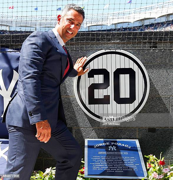 Former New York Yankee Jorge Posada poses for a photograph with his retired number plaque in Monument Park during a ceremony before the Yankees play...