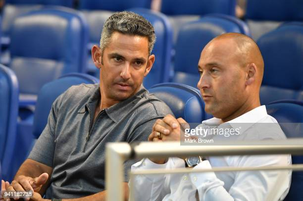 Former New York Yankee Jorge Posada visits with CEO of the Miami Marlins Derek Jeter during the game against the Boston Red Sox at Marlins Park on...