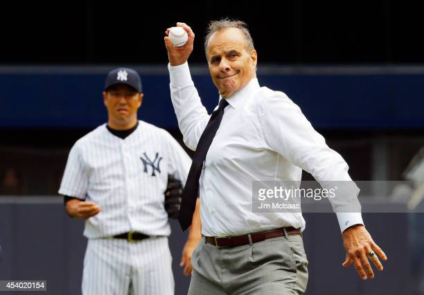 Former New York Yankee manager Joe Torre throws out the ceremonial first pitch before a game against the Chicago White Sox as Hiroki Kuroda looks on...