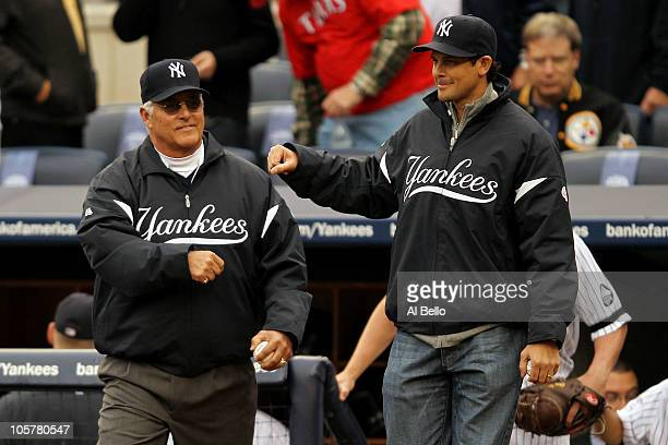 Former New York Yankees Bucky Dent and Aaron Boone walk onto the field to throw out the cermonial first pitch prior to the Yankees playing against...