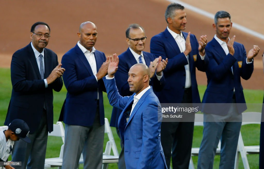 Former New York Yankees great, Derek Jeter waves to the crowd as his father Charles and former teammates Mariano Rivera, manager Joe Torre, Andy Pettitte and Jorge Posada applaud during a pregame ceremony honoring him and retiring his number 2 at Yankee Stadium on May 14, 2017 in New York City.