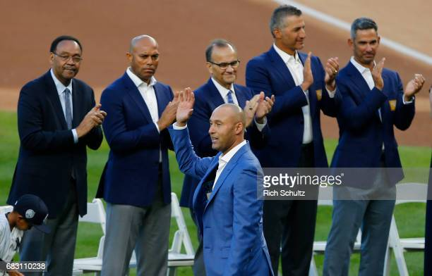Former New York Yankees great Derek Jeter waves to the crowd as his father Charles and former teammates Mariano Rivera manager Joe Torre Andy...