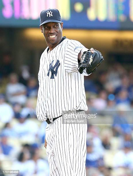 Former New York Yankees pitcher Dwight Gooden smiles and points as he pitches against the Los Angeles Dodgers in an Old Timers game before the game...