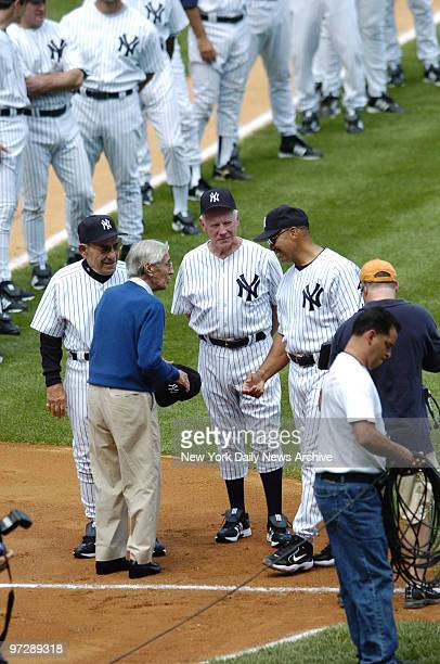 Former New York Yankees' shortstop Phil Rizzuto talks with former Yanks' catcher and manager Yogi Berra pitcher Whitey Ford and outfielder Reggie...