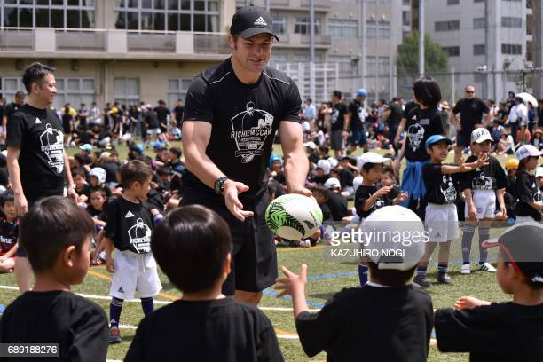 TOPSHOT Former New Zealand All Blacks captain Richie McCaw conducts a ball pass with children during his rugby clinic in Tokyo on May 28 2017 McCaw...