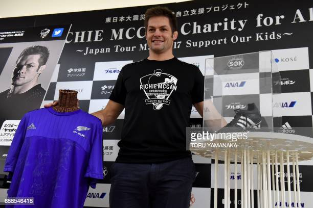 Former New Zealand All Blacks captain Richie McCaw displays a pair of his rugby shoes and a jersey with autographs of All Blacks players which he...