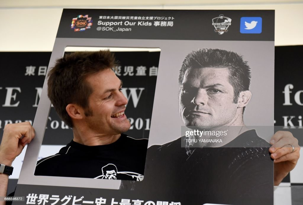 Former New Zealand All Blacks captain Richie McCaw poses with an image of himself during a press conference in Tokyo on May 26, 2017. McCaw is here to raise charity funds for children affected by the massive 2011 earthquake and tsunami in northern Japan. / AFP PHOTO / Toru YAMANAKA