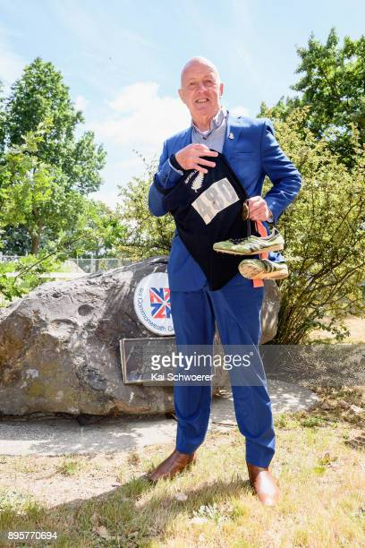 Former New Zealand runner Dick Tayler poses with his old shirt his running shoes and the 1974 Christchurch Commonwealth Games gold medal during a...