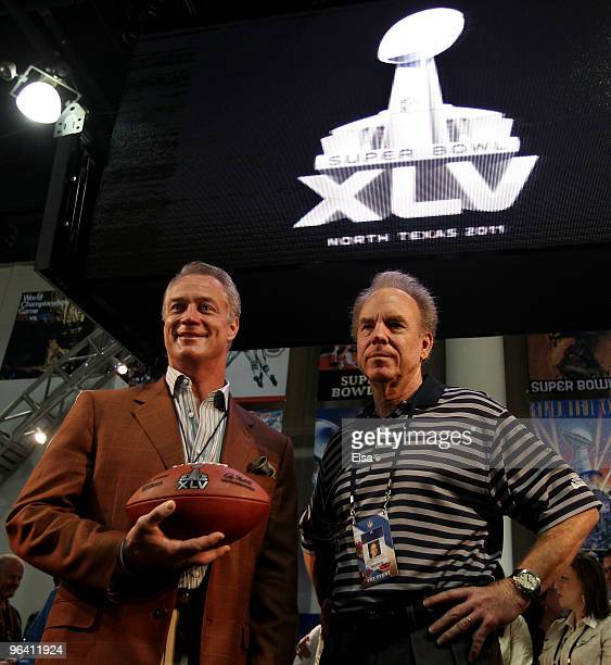 Former NFL fullback Daryl Johnston and former NFL quarterback Roger Staubach hold a football with the new Super Bowl logo during a press conference...