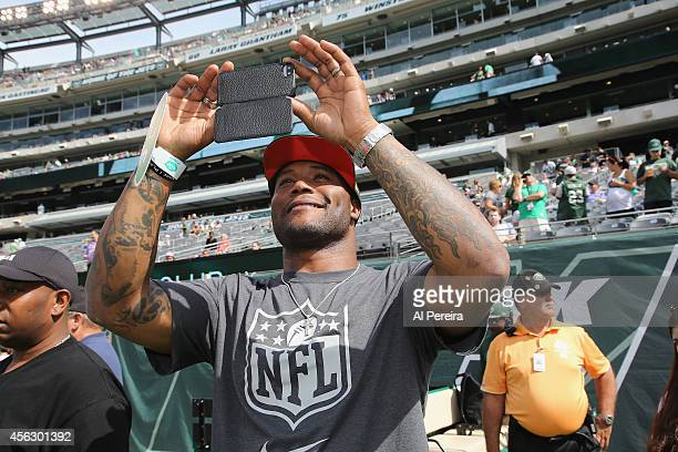Former NFL player and current NFL Network personality Michael Robinson takes a photo when he attends the Detroit Lions vs New York Jets Game at...
