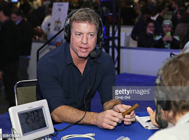 Former NFL player and sportscaster Troy Aikman visits the SiriusXM set at Super Bowl 50 Radio Row at the Moscone Center on February 4 2016 in San...