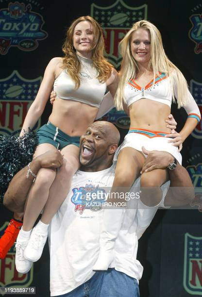 Former NFL player Bob Sapp poses for a photograph with NFL cheerleaders during a photo session at a Tokyo's discotheque in Tokyo 27 Juen 2003 to...