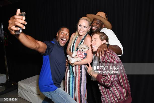 NFL player Martellus Bennett former NFL player Michael Strahan wrestler Roman Reigns and NFL player Travis Kelce pose in the Green Room at the...