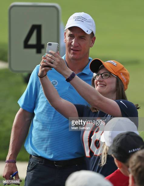 Former NFL player Peyton Manning takes a selfie with a fan during the ProAm prior to The Memorial Tournament presented by Nationwide at Muirfield...