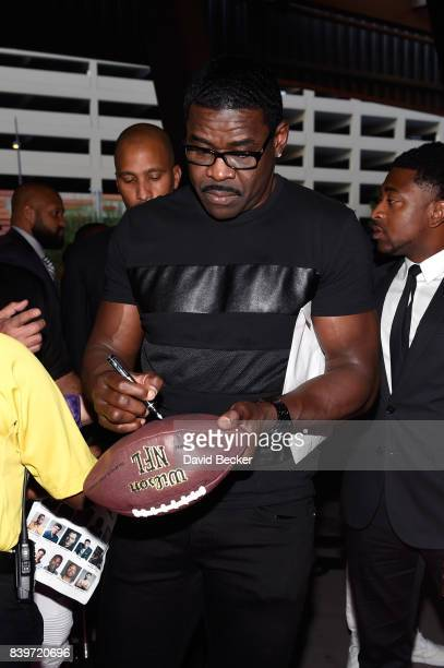 Former NFL player signs a football on TMobile's magenta carpet duirng the Showtime WME IME and Mayweather Promotions VIP PreFight Party for...