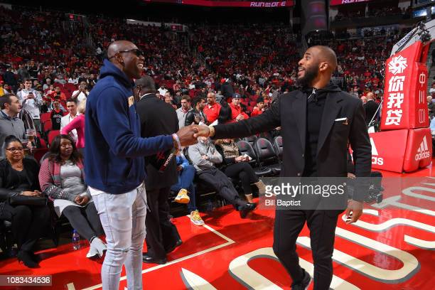 Former NFL Player Terrell Owens and Chris Paul of the Houston Rockets shake hands during a game between the Brooklyn Nets and the Houston Rockets on...