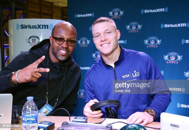 Former NFL player Torry Holt and Christian McCaffrey of the Carolina Panthers attend SiriusXM at Super Bowl LII Radio Row at the Mall of America on...