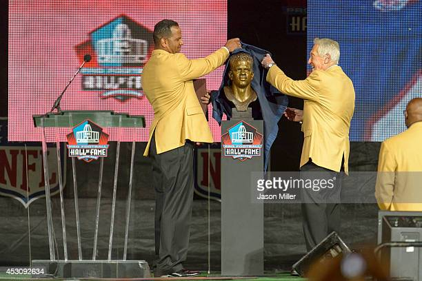 Former NFL wide receiver Andre Reed left unveils his bust with his former coach Marv Levy right during the NFL Class of 2014 Pro Football Hall of...