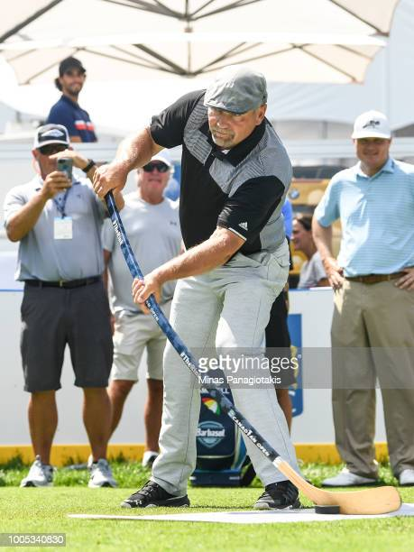 Former NHL hockey player Wendel Clark takes a shot with a hockey stick during the practice rounds at the RBC Canadian Open at Glen Abbey Golf Club on...