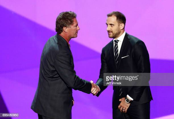Former NHL player Bobby Carpenter and Nick Foligno of the Columbus Blue Jackets shake hands onstage during the 2017 NHL Awards Expansion Draft at...