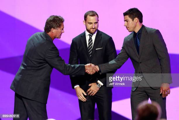Former NHL player Bobby Carpenter and Travis Hamonic of the New York Islanders shake hands onstage during the 2017 NHL Awards Expansion Draft at...