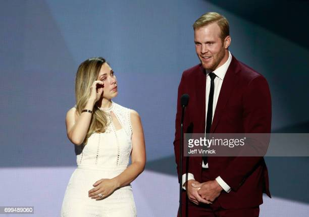 Former NHL player Bryan Bickell speaks onstage as wife Amanda wipes her eyes during the 2017 NHL Awards Expansion Draft at TMobile Arena on June 21...