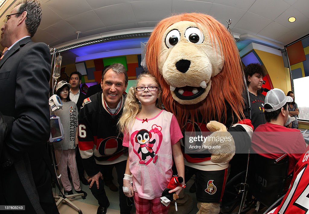 Former NHL player Laurie Boschman and Spartacat visit with a young patient at the unveiling of the NHL All-Star Legacy Playroom at Children's Hospital of Eastern Ontario on January 27, 2012 in Ottawa, Canada.