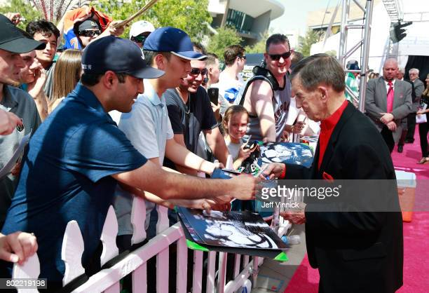 Former NHL player Ted Lindsay signs an autograph for a fan as Lindsay arrives on the magenta carpet for the 2017 NHL Awards at TMobile Arena on June...