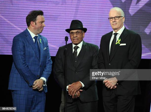 Former NHL player Willie O'Ree presents the inaugural Willie O'Ree Community Hero Award as sportscasters Elliotte Friedman and Scott Oake look on...