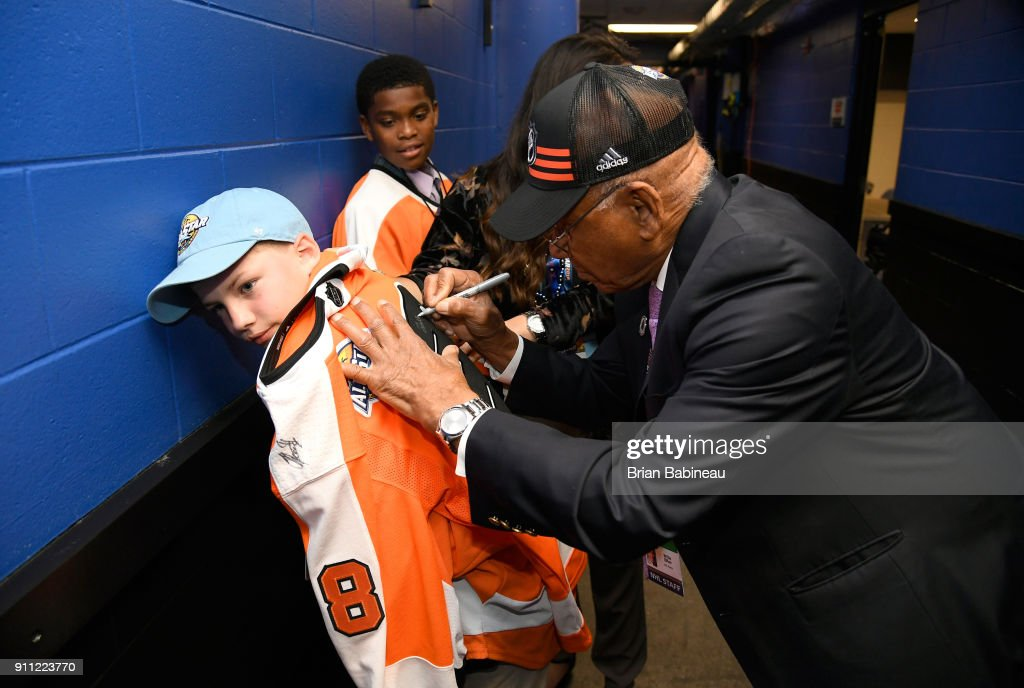 Former NHL player Willie O'Ree signs an autograph for Justin Brass prior to the 2018 GEICO NHL All-Star Skills Competition at Amalie Arena on January 27, 2018 in Tampa, Florida.