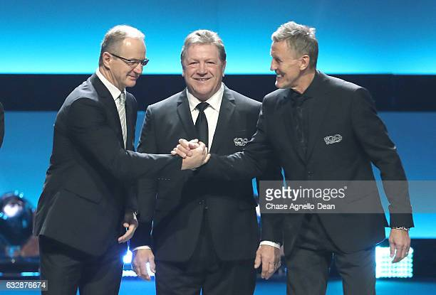 Former NHL players Al MacInnis left shakes the hand of Borje Salming right onstage as Denis Potvin looks onstage during the NHL 100 presented by...